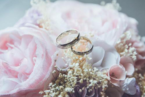 two wedding rings on top of pink roses